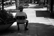 Rear View Of Man Sitting On Chair At Sidewalk