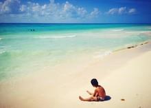 Boy Sitting On Sandy Beach