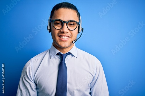 Photo Young brazilian call center agent man wearing glasses and tie working using headset with a happy and cool smile on face