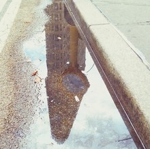 Reflection Of Flatiron Building On Puddle At Street