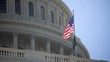 Extreme closeup of the US Capitol dome with a US and POW flags blowing in the breeze.