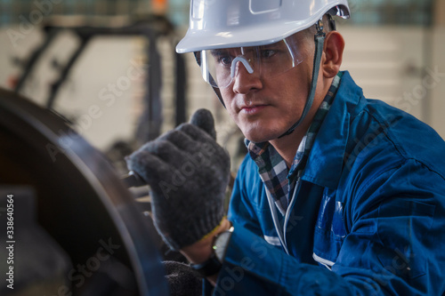 Fototapeta industrail background of caucasian mechanics engineer operating lathe machine fo