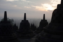 Silhouette Stupas At Borobudur Temple Against Cloudy Sky During Sunset