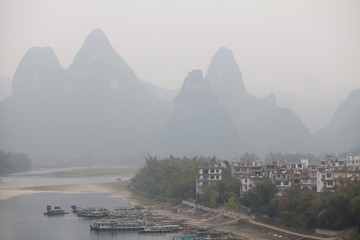 High Angle View Of Ferry Boats Moored In River Against Mountains In Foggy Weather