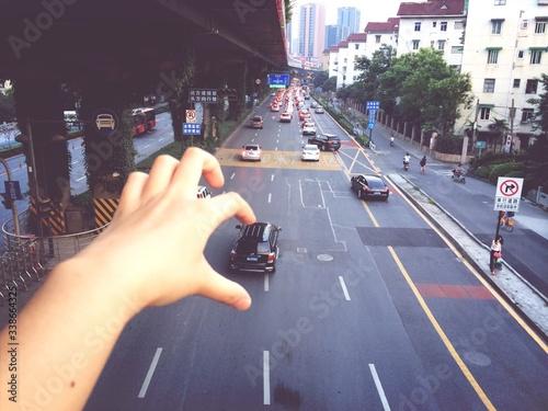 Fototapeta premium Złudzenie optyczne ręki pobierającej samochód z drogi