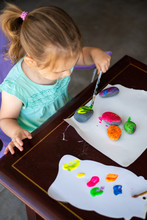 Child In A Teal Shirt Painting Rocks Colorful Colors, Art Activity For A Young Toddler Or Older Child