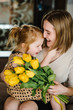 Happy mother's day. Child daughter congratulates mom and gives her a bouquet of flowers tulips at home. Mum and girl smiling and hugging. Family holiday and togetherness. Side view.