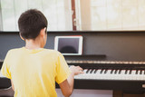 Little boy learning practicing piano online digital tablet