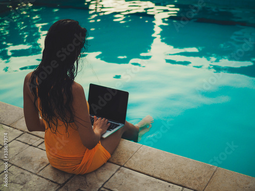 remote online working digital nomad women from the back with long hair and lapto Fototapeta