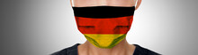 German COVID-19 Masks Flag On PPE Doctor Wearing Mask Panoramic Banner. Coronavirus Pandemic Outbreak In Germany. Graphic Design Illustration Print On Medical Personal Protective Equipment.