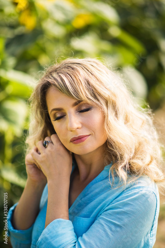 Tela Vertical close-up portrait of beautiful blonde 40 years old woman with closed eyes in blue shirt touching her earring outdoors in back light