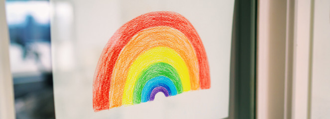COVID-19 rainbow drawing in window displayed for spreading positivity during coronavirus quarantine lockdown. Children giving hope and staying home happy. banner panoramic.
