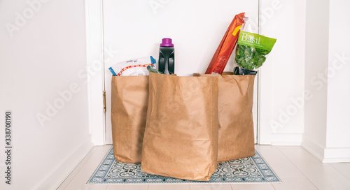 Fototapeta Grocery online delivery receiving grocery bags at home entrance door outside doorstep hallway contactless reception of food deliveries during quarantine COVID-19 Coronavirus. obraz