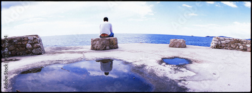 Photo Rear View Of Man Sitting On Rock At Beach