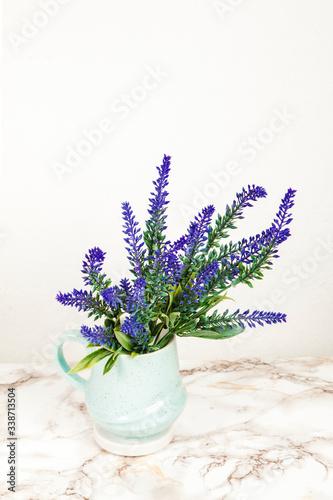 Fototapeta Lavender flowers in a mug on a marble table obraz na płótnie