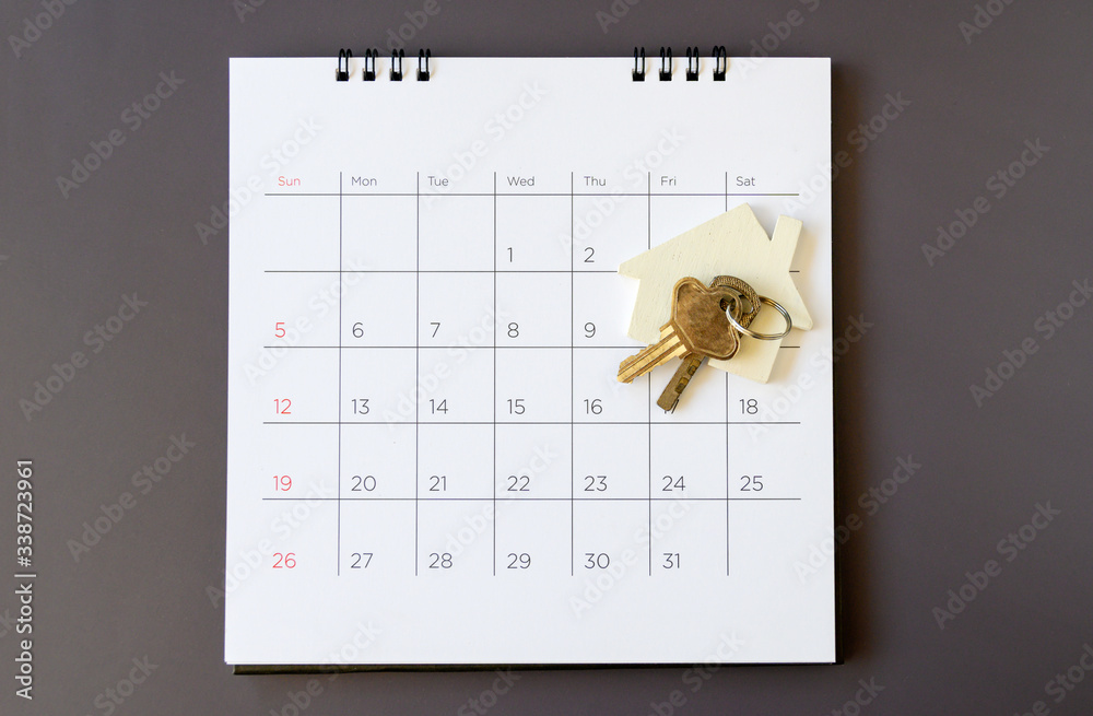 Fototapeta Calendar and house on table. Day of buying or selling a house or payment for rent or loan.