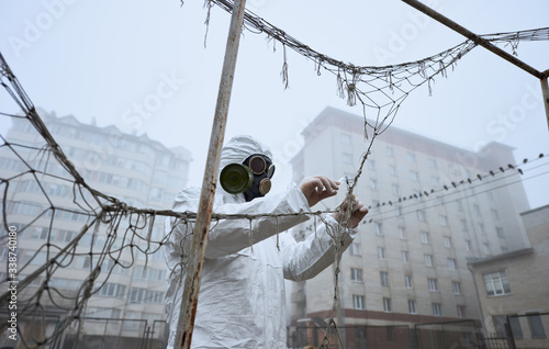 Obraz From below view of male scientist in gas mask and protective clothing monitoring abandoned football pitch, fog, buildings around. Man taking piece of goal net using tweezers and putting in test tube. - fototapety do salonu