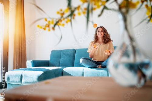 Fototapeta Charming beautiful young girl with curly hair and a happy smile juggles tangerines while sitting on a blue sofa in her living room at home, having fun staying at home obraz