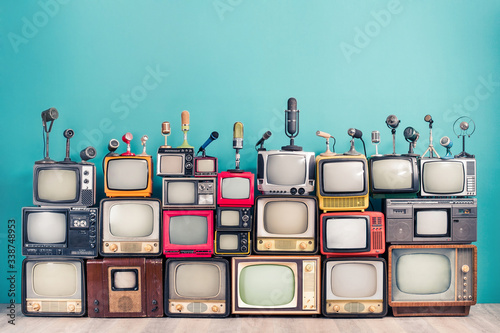 Tela Retro TV receivers set from circa 60s, 70s and 80s of XX century, old classic microphones for press conference front mint blue wall background
