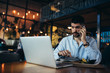 man using laptop and talking on mobile phone while having lunch in restaurant