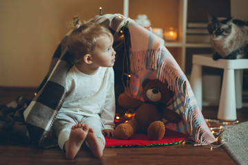 Cute adorable baby reading book in house or fort made of blankets and garlands.
