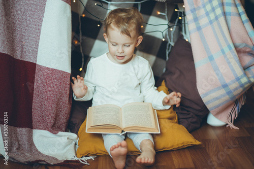 Photo Cute adorable baby reading book in house or fort made of blankets and garlands