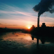 View Of Smoke Stacks From River At Sunset