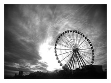 Low Angle View Of Silhouette Ferris Wheel Against Clouds