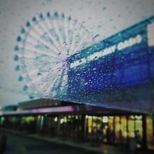 Ferris Wheel In City Seen Through Wet Umbrella At Dusk