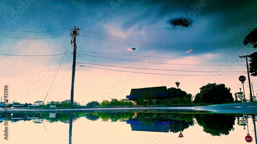 Photo Reflection Of Electricity Pylon And Cloudy Sky On Puddle