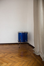 A Blue Drum Stands In A Corner On The Floor Against A White Wall Background. Graphic Resource, Free Space