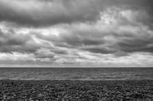 Beach Overlooking Calm Sea Under Grey Sky