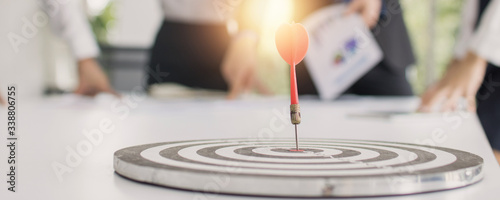 Obraz target and goal concept, dart on board with business people group meeting. - fototapety do salonu