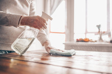 Close Up Of Cleaning Home Wood Table, Sanitizing Kitchen Table Surface With Disinfectant Antibacterial Spray Bottle, Washing Surfaces With Towel And Gloves. COVID-19 Prevention Sanitizing Inside.
