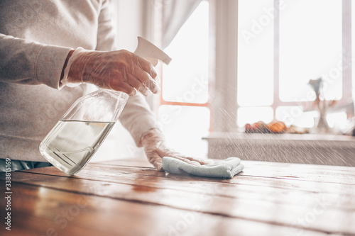 Close up of cleaning home wood table, sanitizing kitchen table surface with disinfectant antibacterial spray bottle, washing surfaces with towel and gloves Fototapete