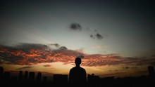 Silhouette Of Man Overlooking City During Sunset