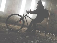 Silhouette Of Person On Bicycle In Abandoned House