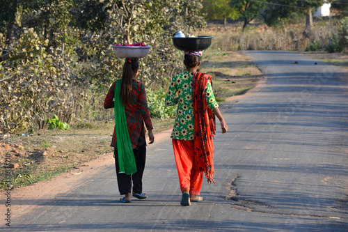 Two girls walking on the street, An Indian rural scene. Wallpaper Mural