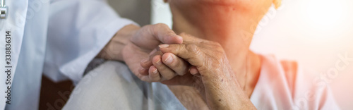 Obraz Geriatric doctor or geriatrician concept. Doctor physician hand on happy elderly senior patient to comfort in hospital examination room or hospice nursing home or wellbeing county. - fototapety do salonu