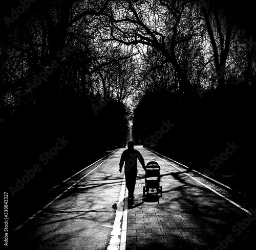 Rear View Of Man Walking With Baby Carriage On Footpath Fototapete