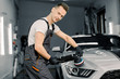 Young handsome smiling Caucasian man, worker of auto detailing service, holds a polisher in the hand and polishes the car, looking and posing at camera. Car detailing and polishing concept