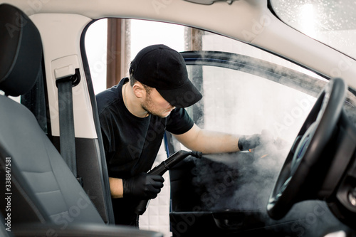 Fototapeta Auto cleaning service and detailing concept. Handsome Caucasian man in black uniform cleaning interior of the car with hot steam cleaner. Selective focus. obraz