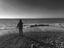 Rear View Of Boy Standing On Beach Against Clear Sky