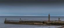 Whitby Lighthouses Amidst Sea At Dusk