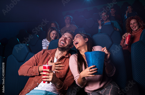 Photo Group of cheerful people laughing while watching movie in cinema.