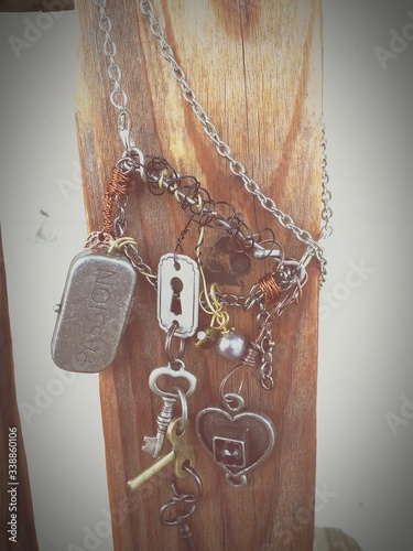 Fotografija Chains And Keys Hanging On Wooden Plank