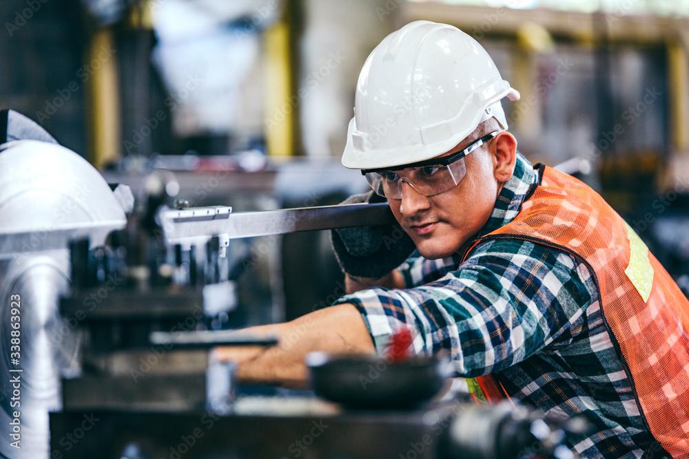 Fototapeta  Male engineer metalworker industrial experienced operator technician worker in safety hard helmet working on lathe machine, professional man in industry technology manufacturing factory workshop