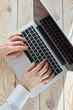 Top view of man's hands typing on laptop in sunny day. Coworking or working at home concept image.