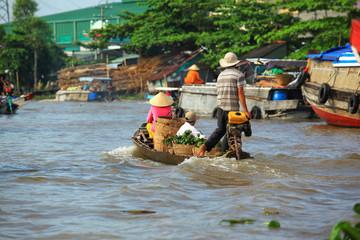 ludzie na łodzi transportujący owoce na rzece Mekong - Wietnam