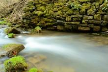 Mossy Rocks On Riverbank
